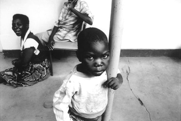 a young orphan boy looking up angrily whilst wrapped around a pole in Africa