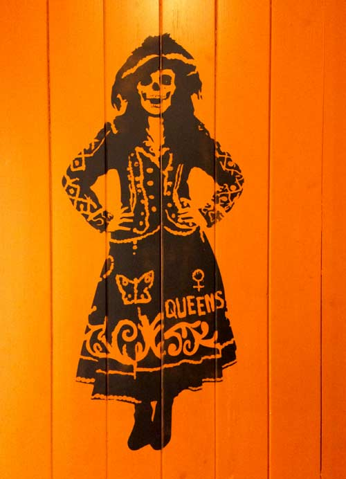 painting of a woman with the head of a skull on an orange door
