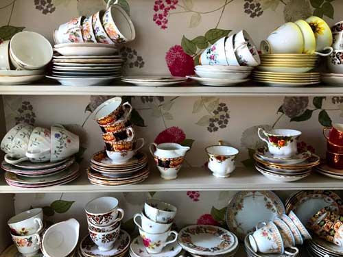 china tea cups piled up on several shelves