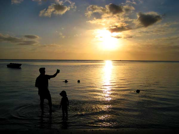 father and child on the beach at sunset in a silhouette