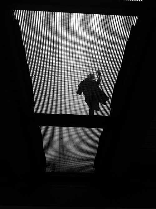 a man walks on a bridge, shot taken from below