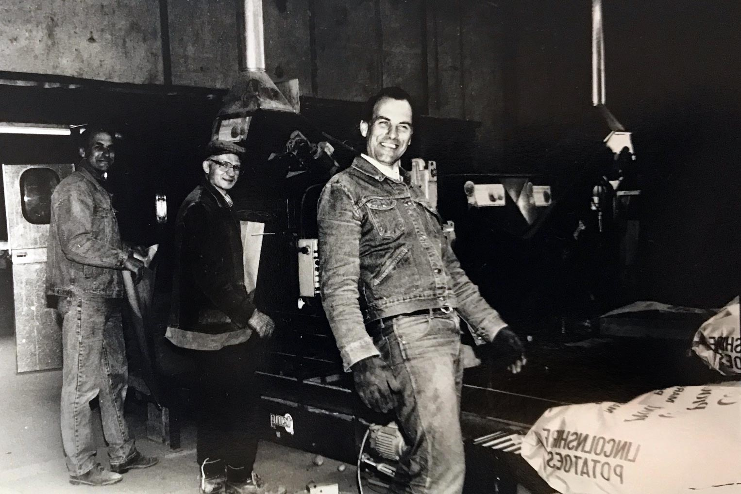 several men working in a factory, one of the men is laughing