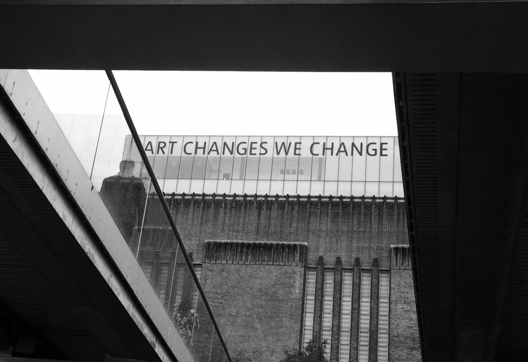 a man walking over a bridge towards an art gallery. the gallery has the words Art Changes We Change written on its building