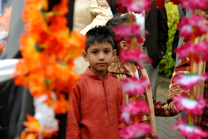 a young boy looks though hanging garlands of flowers