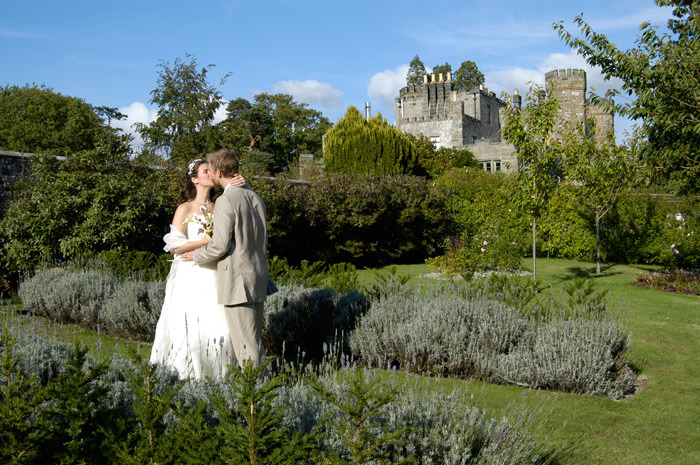 a newly wed couple kiss in the gardens, a castle in the background