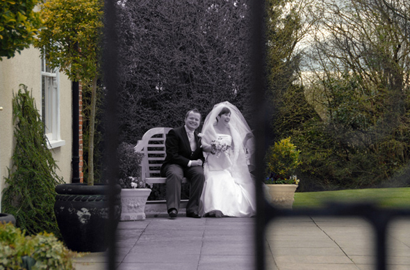 view though metal gate of a bride and groom laughing whilst sitting on a bench
