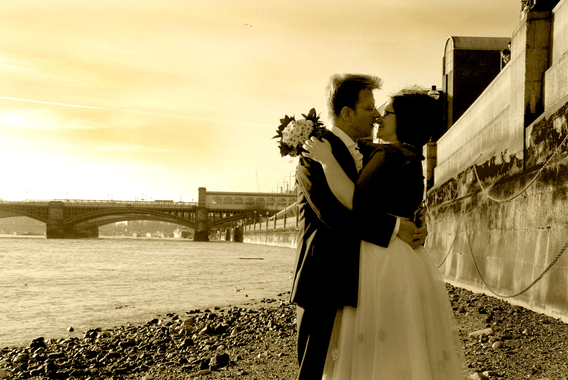 a couple kiss along the bank of the river thames on their wedding day
