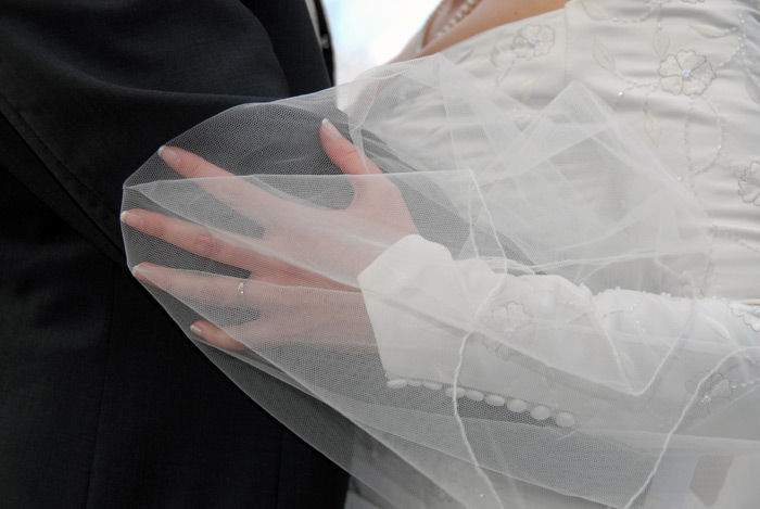 close up of a brides hand covered by her veil holding her grooms arm